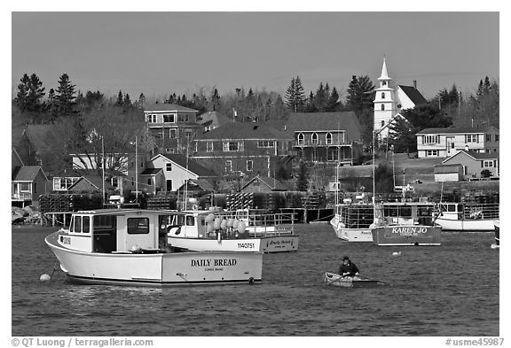 Lobsterman paddling towards boat. Corea, Maine, USA (black and white)