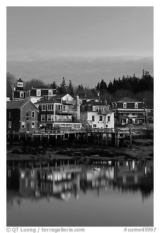 Houses with lights reflected in harbor. Stonington, Maine, USA (black and white)