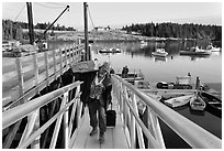 Man carrying construction wood and rolling case out of mailboat. Isle Au Haut, Maine, USA ( black and white)