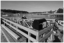 Mailbox and people unloading mailboat. Isle Au Haut, Maine, USA (black and white)