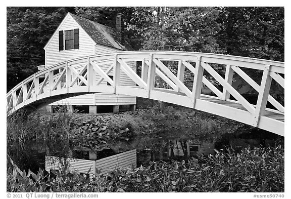 Arched bridge over mill pond. Maine, USA (black and white)
