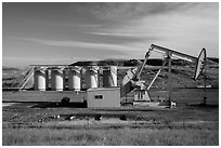 Pumping unit and tanks, oil well. North Dakota, USA ( black and white)