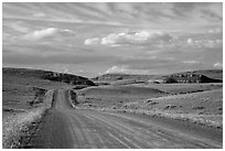 Gravel road, rolling hills and badlands. North Dakota, USA (black and white)