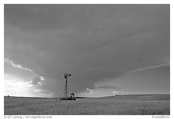 Windmill and tractor under a threatening stormy sky. North Dakota, USA (black and white)