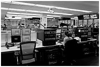 Bloomberg News analyst working in front of many screens. NYC, New York, USA (black and white)