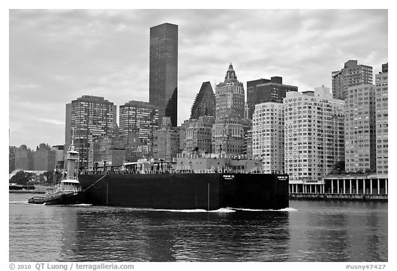 Barge on Hudson River and Manhattan waterfront. NYC, New York, USA (black and white)