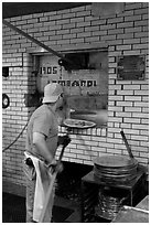 Man loading pizza into oven, Lombardi pizzeria. NYC, New York, USA ( black and white)