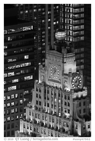 Top of vintage high-rise building with globe and clocks. NYC, New York, USA (black and white)