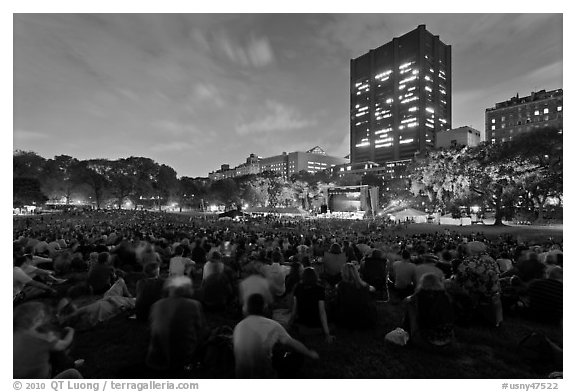 Crowd sitting on lawn during evening outdoor concert, Central Park. NYC, New York, USA (black and white)
