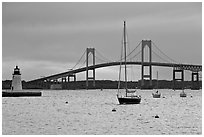 Newport Bridge and Newport Harbor lighthouse at sunset. Newport, Rhode Island, USA ( black and white)