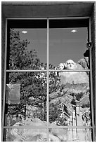 Cliff and sculptures reflected in a window, Mount Rushmore National Memorial. South Dakota, USA (black and white)