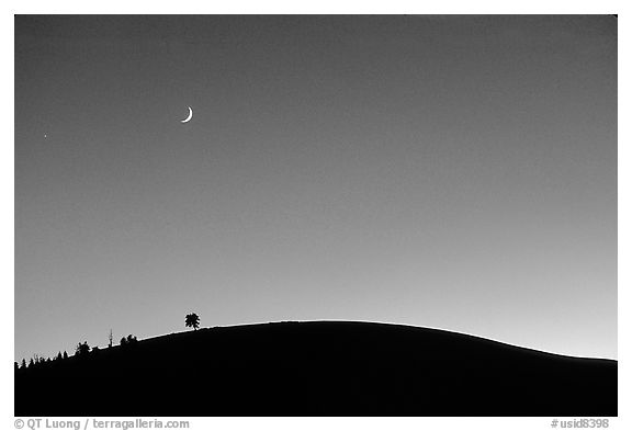Curve of cinder cone, pastel sky, and moon, Craters of the Moon National Monument. Idaho, USA (black and white)