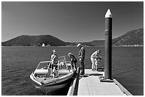 Family boarding boat, East Lake. Newberry Volcanic National Monument, Oregon, USA ( black and white)