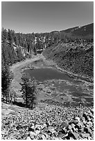 Pond at the edge of big obsidian flow. Newberry Volcanic National Monument, Oregon, USA ( black and white)