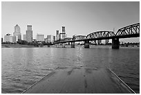 Deck, and Portland skyline with bridge at sunrise. Portland, Oregon, USA (black and white)