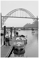 Couple holding small boat at boat lauch ramp. Newport, Oregon, USA (black and white)