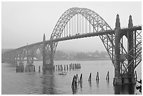 Small boat exiting harbor under Yaquina Bay Bridge. Newport, Oregon, USA (black and white)