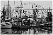 Commercial fishing boats and Yaquina Bay Bridge at dawn. Newport, Oregon, USA (black and white)