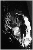 Boy and man exploring sea cave. Bandon, Oregon, USA (black and white)