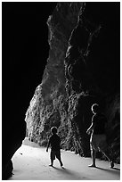 Father and son walking towards the light in sea cave. Bandon, Oregon, USA (black and white)