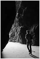 Woman walking out of sea cave. Bandon, Oregon, USA (black and white)