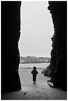 Infant standing at sea cave opening. Bandon, Oregon, USA (black and white)