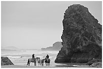 Women ridding horses next to sea stack. Bandon, Oregon, USA (black and white)
