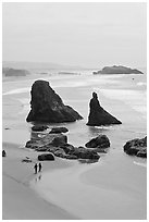 Beach with couple walking amongst sea stacks. Bandon, Oregon, USA (black and white)