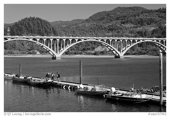 Small boat deck and Rogue River bridge. Oregon, USA (black and white)