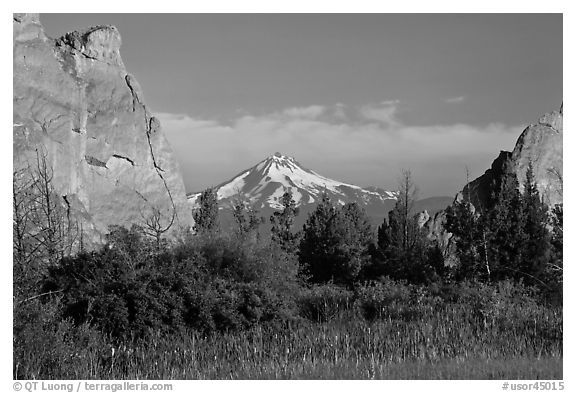Snow-capped volcano seen between rock pinnacles. Smith Rock State Park, Oregon, USA (black and white)