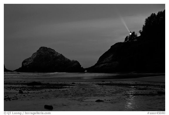 Heceta Head and lighthouse beam from beach by night. Oregon, USA (black and white)