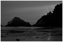 Heceta Head and lighthouse beam from beach by night. Oregon, USA ( black and white)