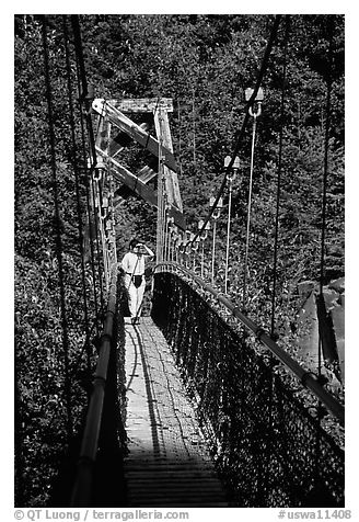 Woman hiking on suspension bridge, Lava Canyon. Mount St Helens National Volcanic Monument, Washington