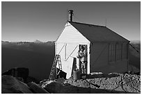 Man standing in doorway of Hidden Lake lookout. Washington (black and white)