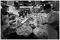 Countermen unloading seafood,  Pike Place Market. Seattle, Washington (black and white)