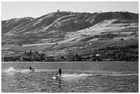 Personal watercraft riders and vineyard covered hills, Lake Chelan. Washington ( black and white)