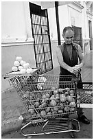 A man peels oranges to make an orange drink, which is drunk from the fruit itself, Ponce. Puerto Rico (black and white)