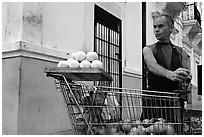 Man peeling oranges to make a drink, drunk from the fruit itself, Ponce. Puerto Rico (black and white)