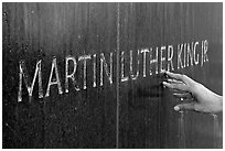 Hand touching the letters Martin Luther King on the Civil Rights Memorial wall. Montgomery, Alabama, USA ( black and white)
