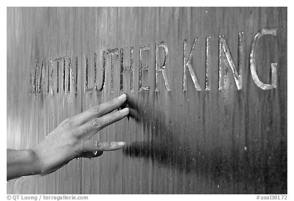 Hand touching the letters Martin Luther King in flowing water. Montgomery, Alabama, USA (black and white)
