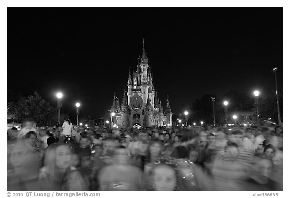 Crowds on Main Street with castle in the back at night. Orlando, Florida, USA (black and white)
