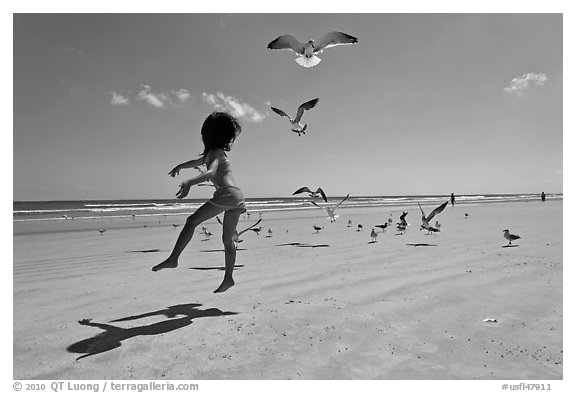 Girl jumping on beach with seagulls flying, Jetty Park. Cape Canaveral, Florida, USA (black and white)