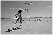 Girl jumping on beach with seagulls flying, Jetty Park. Cape Canaveral, Florida, USA ( black and white)