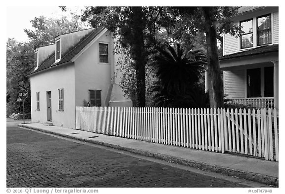 White picket fence and houses on cobblestone street. St Augustine, Florida, USA (black and white)