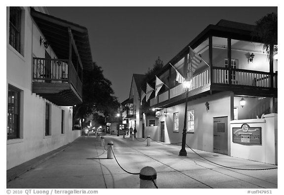 Old street and historic buildings with flags by night. St Augustine, Florida, USA (black and white)