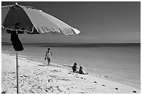 Beach with unbrella, children playing and woman strolling,. The Keys, Florida, USA (black and white)