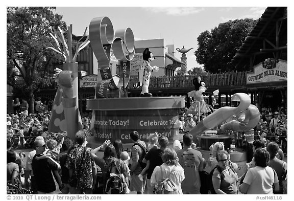 Crowds attends parade with Mickey and Minnie characters. Orlando, Florida, USA (black and white)