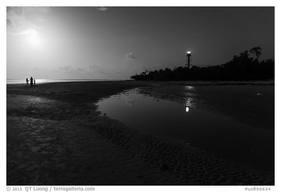 Lighthouse beach with family in distance and moonlight, Sanibel Island. Florida, USA (black and white)
