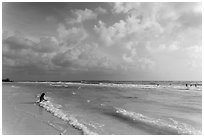 Woman sitting in water, Fort De Soto beach. Florida, USA (black and white)