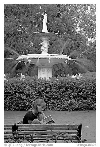Woman sitting on bench with book in front of Forsyth Park Fountain. Savannah, Georgia, USA (black and white)